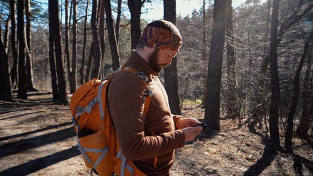 theme tourism and technology. Young caucasian man with beard and backpack. Hiking tourist in pine forest uses technology, hand holding mobile phone to touch the screen. Gps application orientation.