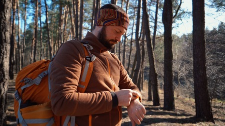 Be on time in travel and adventures. Waist up portrait of bearded man traveler, with backpack, uses technology sports watch for navigating gps electronic compass in forest and looking at his watch.