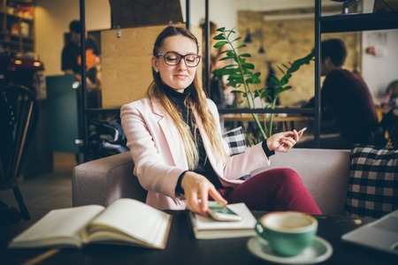 theme modern profession female blogger. Caucasian woman with glasses and jacket sitting inside coffee shop behind wooden table with notebook, laptop and cup coffee. Girl emotion dream, think writer. Stock Photo