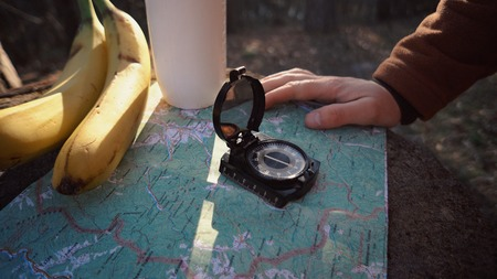 theme hiking and nature travel. Hands Caucasian male tourist break felled tree, stump in forest autumn sunny weather. Searching direction with compass on map. Theme navigation and plot route.