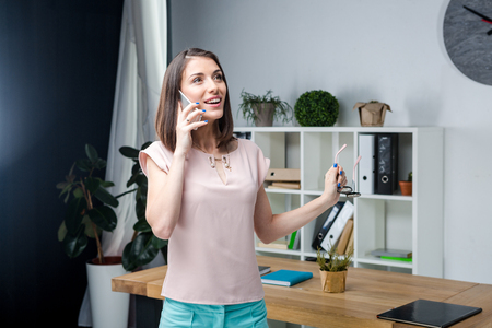 .Subject business woman talking on the phone. Young beautiful caucasian woman hand ear phone call smartphone. Business man stands near the desk in his hand glasses emotion smile happiness and joy.