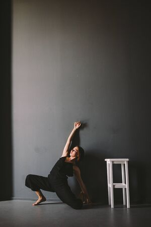 social theme of female loneliness is pain suffering. Abastration of male domestic violence. Young beautiful Caucasian woman in black clothes, strange pose, white chair big dark room. Fear and despair. 写真素材