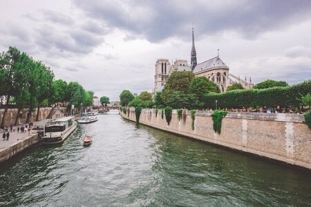July 23, 2017. Paris, France. Notre dame cathedral from river Seine in Paris. Notre dame cathedral from river Seine Paris, France. Beautiful view of a canal-boat and the Notre-Dame Cathedral.