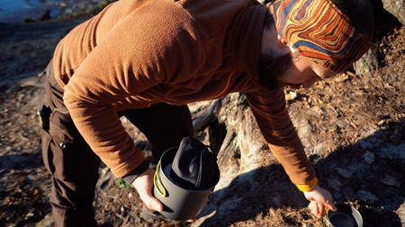 The theme of tourism is hiking and traveling in nature. Hands Caucasian man unpacking, setting the opening of the cover to get the pot kettle for cooking, boil water in the forest.