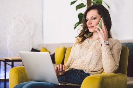 Happy successful businesswoman calling with cell telephone while sitting in coffee shop, smiling female entrepreneur using laptop and having talk with mobile phone in cafe, concept of distant work