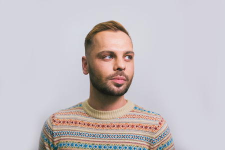 Portrait of a young caucasian stylish and fashionable man with a beard. Homosexual man, gay model posing.