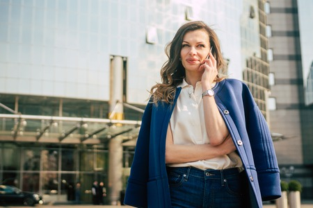 Caucasian business woman speaking by phone. Waist up portrait of a successful European business woman woman, talking on the phone, standing on glass background, modern office building. Sunny weather.