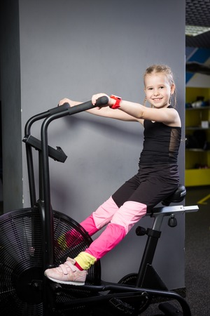 Small attractive caucasian child using exercise bike in the gym. Fitness. A little athlete using an air bike for a cardio workout at the crossfit gym. Sport girl sitting on bicycle machine.
