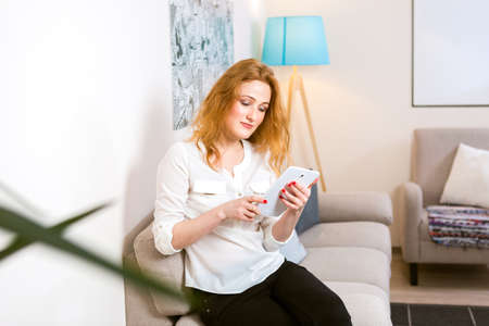 Concept of people, technology and education. Young caucasian female student with redhead long hair and freckles on face sitting on couch and using tablet within room interior.