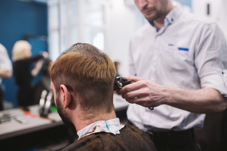 Close up shot of a man getting a trendy haircut at a hair salon. Male caucasian hairdresser serving a client. Man with a beard making haircut with a typewriter and comb.