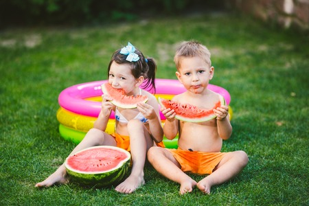 Funny little kids brother and sister eating watermelon on green grass near inflatable pool in yard at home.