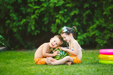 Two children, Caucasian brother and sister, sitting on green grass in backyard of house and hugging big tasty sweet watermelon berry