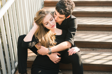Beautiful young multiracial couple, student couple in love, sit wooden staircase in the city. Beautiful Turkish brunette guy hug a Caucasian girl in black clothing. Date young people in sunny weather.