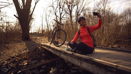 Happy caucasian woman cyclist makes a photo of herself a selfie on the phone while sitting on the bridge over a river in the forest in sunny weather. Imagens