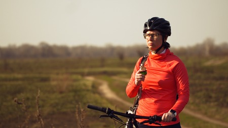 Athletic Caucasian woman eats protein bar ride on mountain bike on nature. Young sporty woman athlete in helmet resting while biting nutritional bar. Fitness woman eating energy snack outdoor. Banque d'images