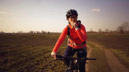 Athletic Caucasian woman eats protein bar ride on mountain bike on nature. Young sporty woman athlete in helmet resting while biting nutritional bar. Fitness woman eating energy snack outdoor. Фото со стока
