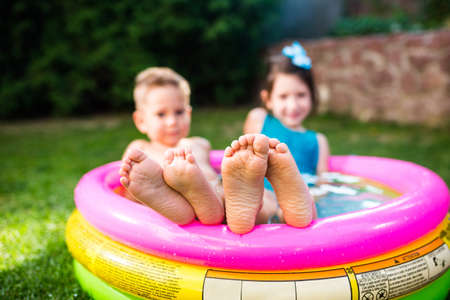 Theme summer vacation. Two children Caucasian brother and sister lie in water, inflatable home round pool in yard on green grass. Close-up of feet sole heels children in hot summer weather. Stockfoto