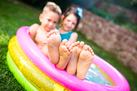 Theme summer vacation. Two children Caucasian brother and sister lie in water, inflatable home round pool in yard on green grass. Close-up of feet sole heels children in hot summer weather. Standard-Bild
