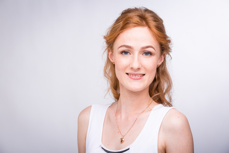 Portrait of a beautiful young female student with a smile in a white shirt of European, Caucasian nationality with long red hair and freckles on her face
