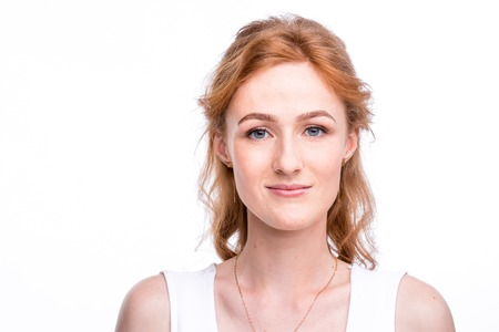 Portrait of a beautiful young woman of European, Caucasian nationality with long red hair and freckles on her face posing on a white background in the studio.