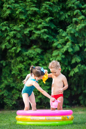 childhood summer games with water pool. Caucasian brother and sister play with plastic toys watering can pouring water splashing, inflatable round childrens bathroom. Summer hot holidays in swimsuits.