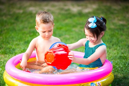 Subject childhood summer games in the yard. Caucasian brother and sister playing plastic toys bucket sitting in the water
