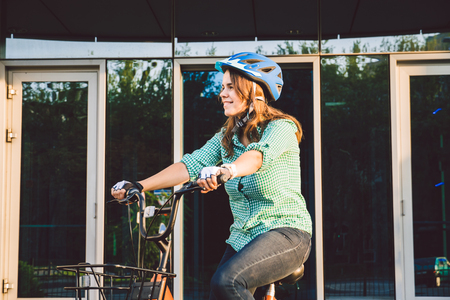 Theme to work on the bike. A young Caucasian woman arrived on environmentally friendly transport bike to the office. Girl in a bicycle parking office building in a helmet, gloves and shirt and jeans.