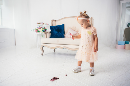 Little funny caucasian child girl dropped on the floor sweetness dessert cake and mess. Kindergarten and birthday party spoiled, fell sweet food on the floor at home. Stock Photo
