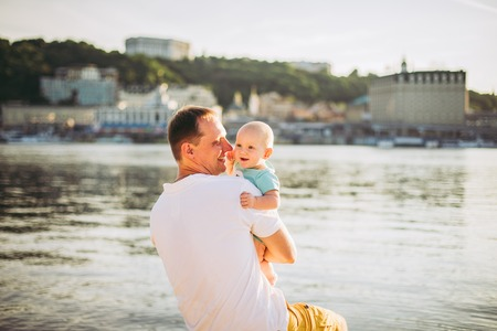 Subject recreation father and little son. Young caucasian dad sits on wooden bench overlooking the town Kiev and holding river of the Dnieper, hugging a toddler baby on sandy beach on the banks pond.