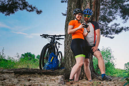Happy couple searching on map in smartphone destination. man and woman in helmets traveling mountain biking over rough terrain. Theme tourism and navigation, search way, create route, gps phone app.