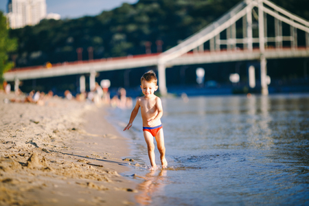 Theme summer outdoor activities near the river on the city beach in Kiev Ukraine. Little funny baby boy running along the river bank, jumping a splash of water sandy beach summer time.
