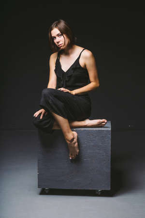 Young Caucasian female model posing in studio black background.Girl sitting in a black dress on a dark wall. Subject severe poor psychological state, intra, problems, personality conflict. 写真素材