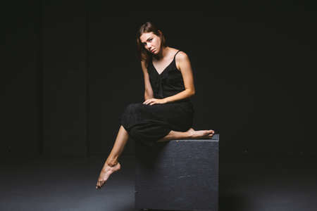 Young Caucasian female model posing in studio black background.Girl sitting in a black dress on a dark wall. Subject severe poor psychological state, intra, problems, personality conflict. Imagens