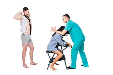The theme relaxation and rest in office. The queue of employees will be waiting for a massage at the invited specialist. Head and neck massage on the chair. Cheerful Caucasian man in shorts and tie.