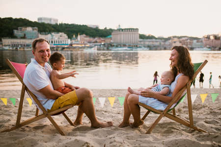 Family at seaside in evening open-air cafe. Mother and father and two sons sit on sun loungers, looking at sunset on sandy beach near river overlooking city. Concept travel and summer family vacation. Archivio Fotografico