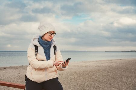 Caucasian woman in hat and jacket with a backpack in winter sits on a wooden pier on beach near the North Sea. Denmark Copenhagen tourist uses a mobile phone on the shore. Scandinavia Travel Theme Imagens