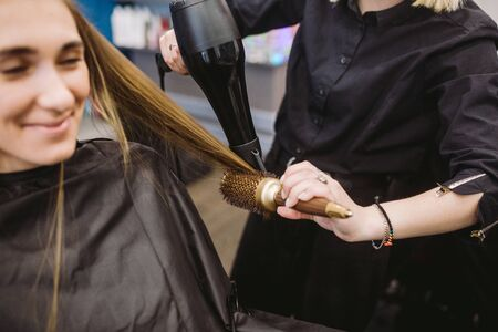 Portrait of happy woman at the hair salon. Professional hair styling concept. Hairdresser drying girl long hair using hairdryer and brush. Drying With Blow Dryer.