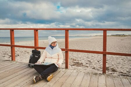 Caucasian woman in hat and jacket with backpack in winter sits on wooden pier on beach near North Sea. Denmark Copenhagen tourist uses paper map shore. Theme Travel and Navigation in Europe.