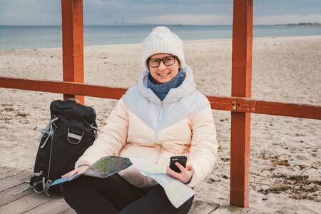 Woman Traveler With A Backpack, Map And Phone. Theme Travel and Navigation in Europe. Girl in hat and jacket with a backpack in winter sits on a wooden pier on the beach near the North Sea. Imagens