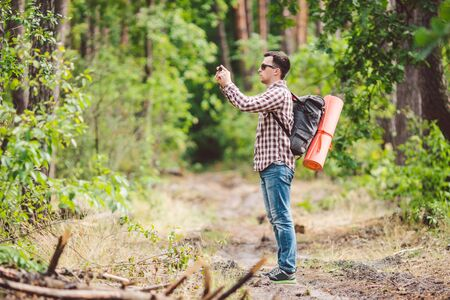 Man hiker taking photo smart phone in forest. Attractive Traveler Making Photo With Mobile Phone. Traveler hiker man with backpack hiking in nature, tourist backpacker use camera. vacation concept.