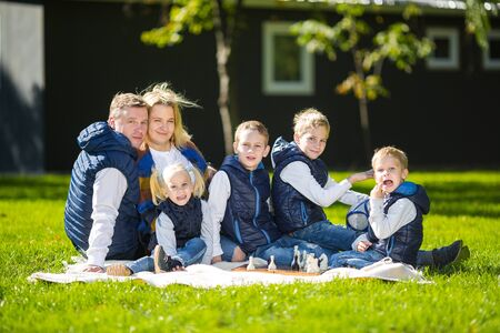 Big Family Relaxing In Green Nature. Happy family portrait on outdoor, group six people sit on grass, summer season, child and parent. Children, parenthood and nature concept. picnic outdoors on lawn.