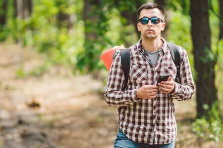 Hipster young man with backpack using smart phone on beautiful nature.Travel concept. Outdoor travel. Travel and explore. Backpacker male Going in forest Gps Route. Portrait hiker using mobile phone.