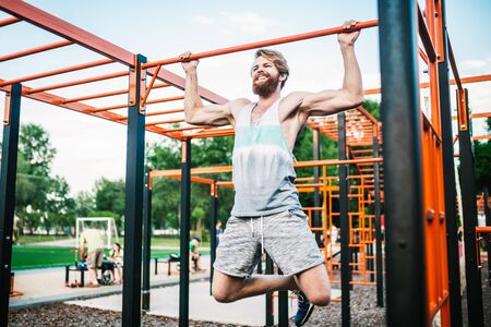 strong athlete doing pull-up on horizontal bar. Muscular man doing pull ups on horizontal bar in park. Gymnastic Bar During Workout. training strongmanoutdoor park gym. Man Doing Exercise gym Outdoor. 写真素材