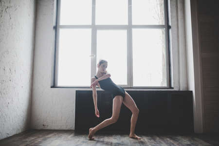 Plasticity slim woman dancing near window. Professional dancer enjoy dance. Lady Dancer Training Modern Ballet In Class. Contemporary dance performer. Daylight, silhouette beautiful body. Dance theme. Banque d'images
