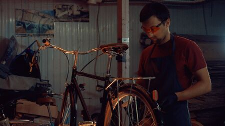 theme small business bike repair. A young Caucasian brunette man wearing safety goggles, gloves and an apron uses a hand tool to repair and adjust the bike in the workshop garage.