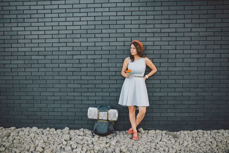 cheerful girl in dress holding take away cup. Hipster model wearing stylish summer outfit Outdoors. woman with backpack walks along city street. hipster girl on brick wall,lifestyle of modern teenage.