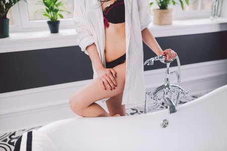 Woman In Bathroom. beautiful girl on bathtub in underwear. Sex woman taking relaxing bath in hot tub. Beautiful sexy lady elegant white shirt in bathroom. Fashion portrait model on bath indoors.