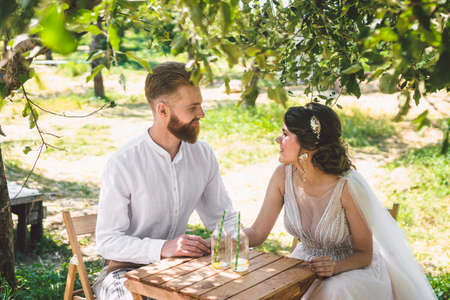 Attractive couple newlyweds, happy and joyful moment. bride and groom sit at table set for two in woods. Concept romantic date. Wedding couple sitting in cafe table and lovingly look at each other.