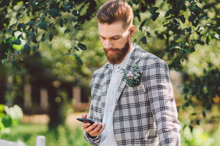 sexy bearded man groom with beautiful haircut with phone in hand. Model with a stylish haircut in a checkered jacket and beard uses a phone on a background of wood, park and forest in sunny weather.
