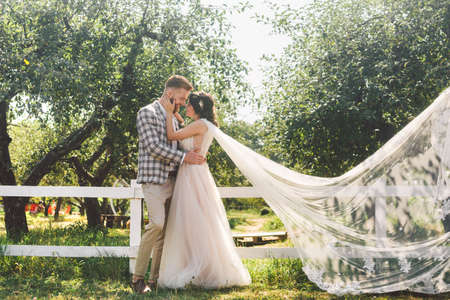 Caucasian couple in love bride and groom standing in embrace near wooden white, rural fence in park an apple orchard. theme is wedding portrait and beautiful wedding white dress with long veil.